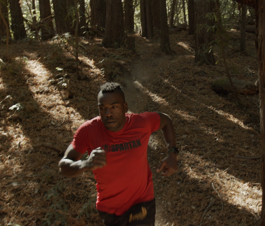 Triathlete Max Fennell running through a wooded area in California