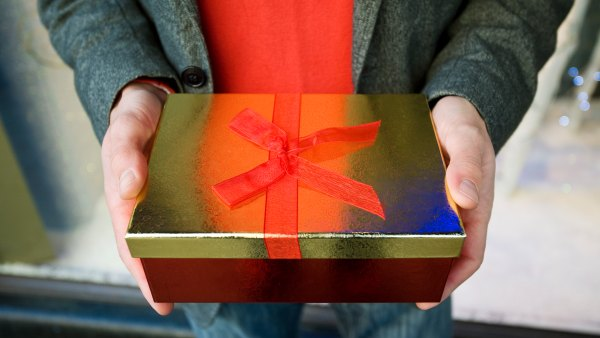 Close-up of a man holding a festive gift box outside the Harrods department store in London, Knightsbridge, London, London, England.
