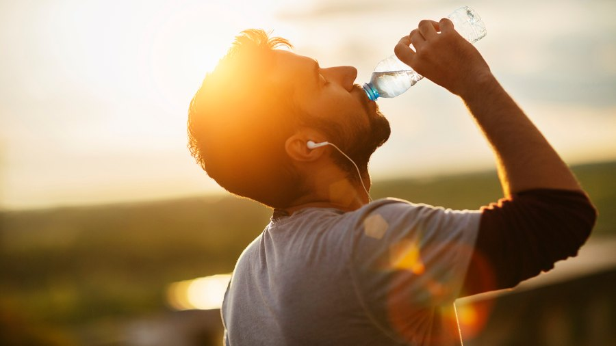 Close up of a young man drinking water from a plastic bottle underneath a clear sky. He is listening to music from small white earphones and his eyes are closed. The sun is shining strong in the background.
