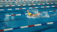Young male swimmer doing butterfly stroke in swimming lane, side view (Photo by Black 100/Getty Images)