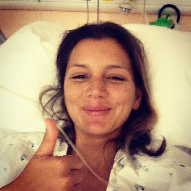 Maya Gabeira gives a thumb's up from her Portuguese hospital bed after nearly drowning in a surfing accident at Nazare North Canyon