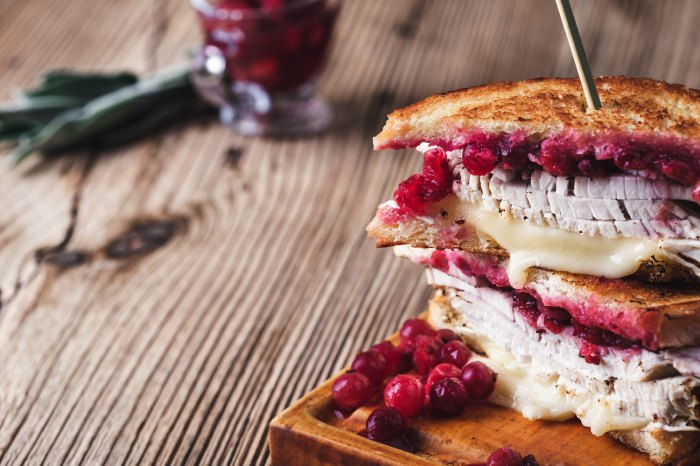 Thanksgiving turkey sandwich with brie cheese and cranberry sauce on cutting board.
