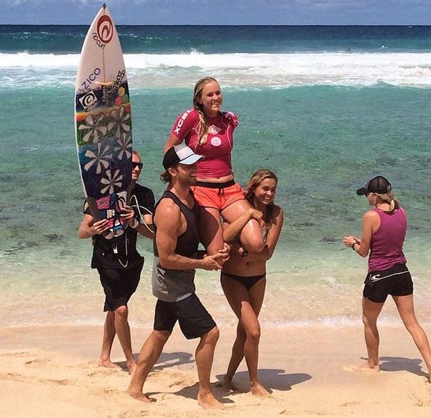 Bethany Hamilton is carried up the beach by her husband Adam and friend after winning the Surf-n-Sea Pipe Pro; photo courtesy Bethany's Facebook page.