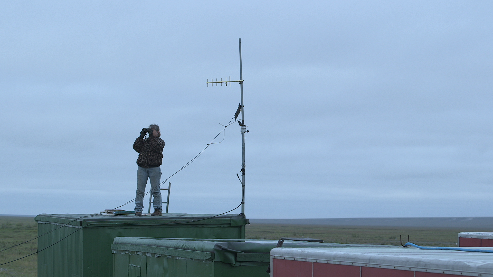 """""""Life Below Zero"""" star Sue Aikens, standing on her """"perch"""" at Kavik River Camp, is constantly scanning the horizon to keep an eye out for grizzly bears."""