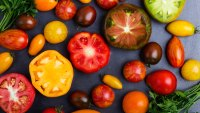 Colorful ripe heirloom tomatoes over gray table viewed from above