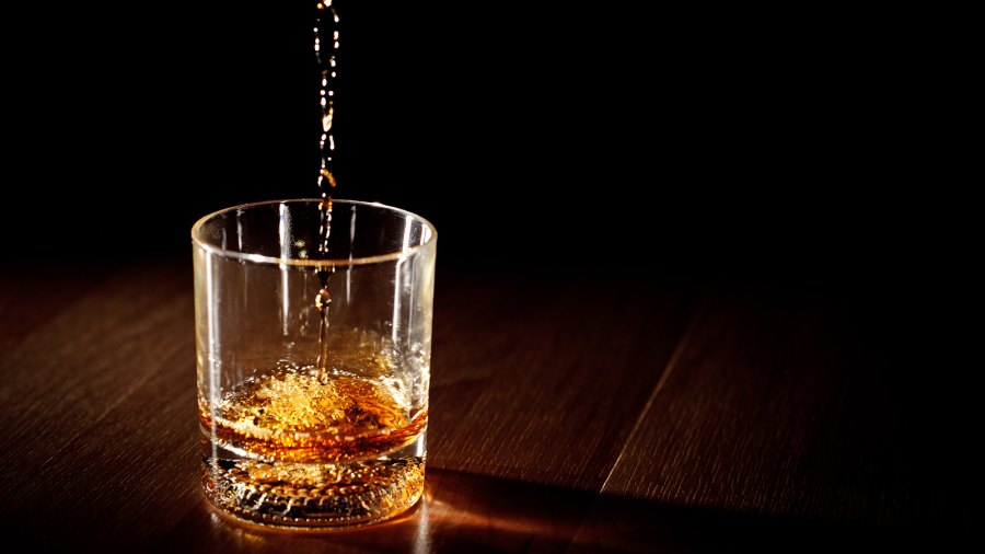 Scotch or bourbon whiskey (or whisky) being poured into a glass with dramatic studio lighting and a black background.