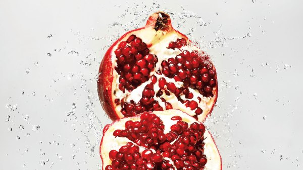 Pomegranate cut in half with water splashing behind it
