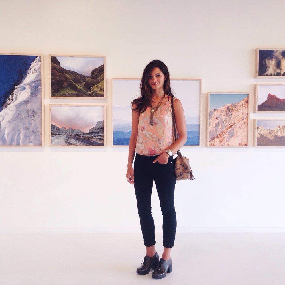 Meg Haywood-Sullivan poses in front of a gallery of her photography Photo courtesy of Haywood-Sullivan