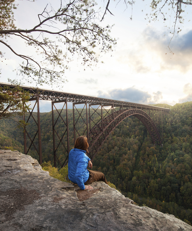 fayetteville Kaare Iverson sits at the edge of Bridge Buttress in New River Gorge, West Virginia and enjoys a sunset over the longest arch bridge in North America. Photo: Kaare Iverson / Tandem Stock