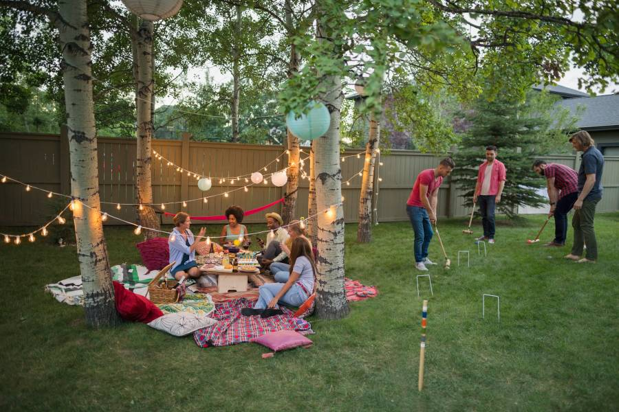 Friends playing croquet and eating at backyard party