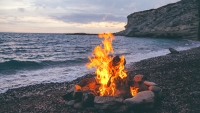 Summer Camp fire burning in stones on the pebble beach and against sea coast line, rocks and sunset sky.