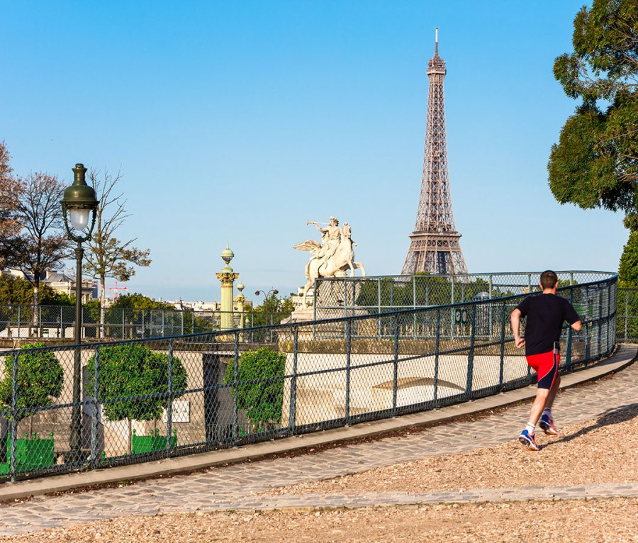 Jogging through Tuileries Garden in Paris with the Eiffel Tower in the distance
