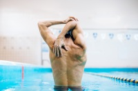 Muscular swimmer stretching in pool
