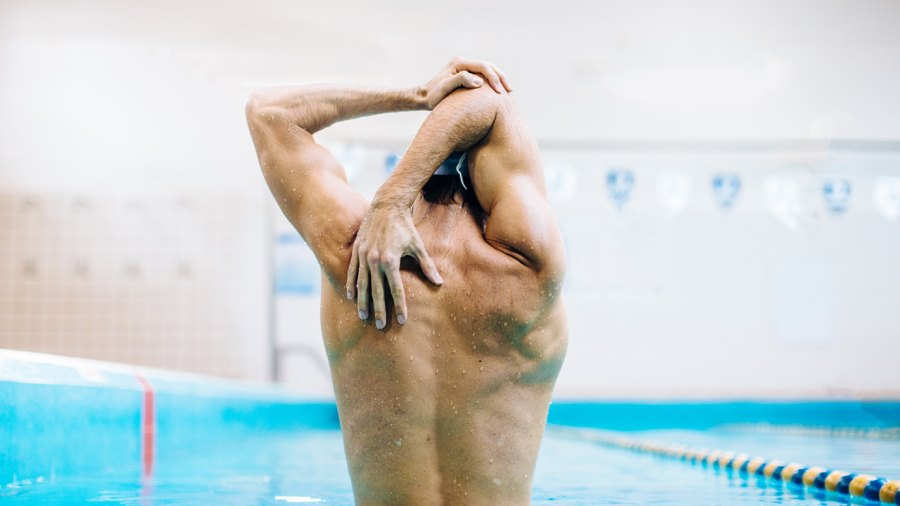 Swimming Workouts: Muscular swimmer stretching in pool