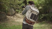 The Solar Paper charger hangs on a backpack