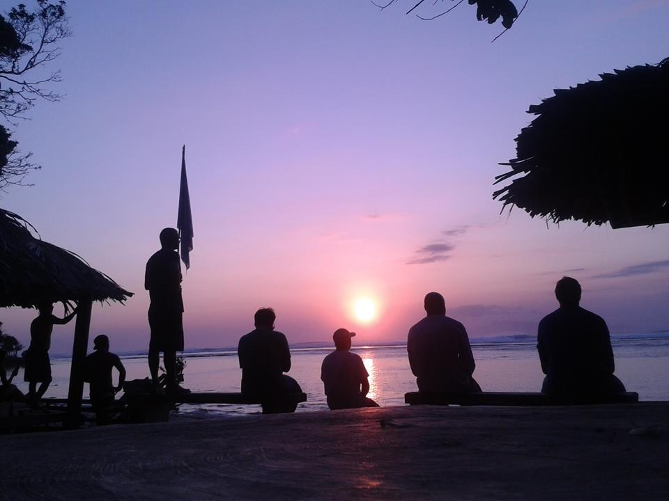 After a day of surfing guests watch the sun set over the waves. Photo by Bobby's