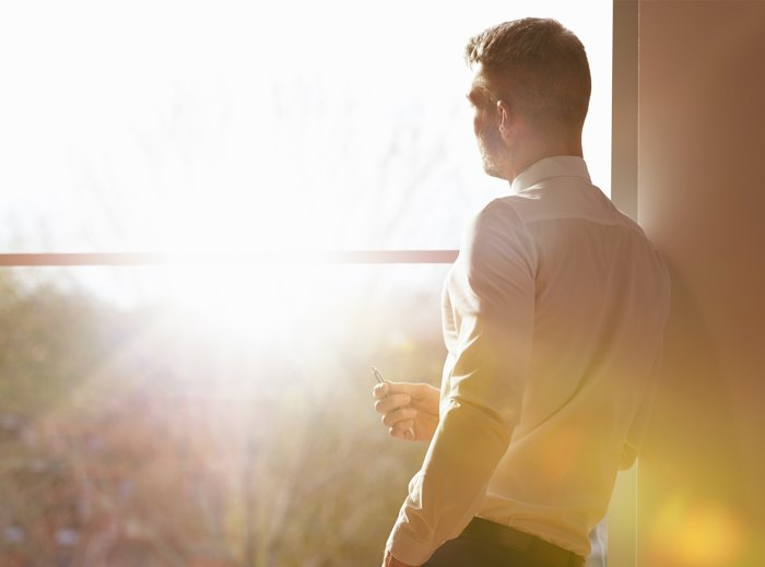 business man standing my window with sunlight