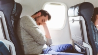 Young man sleeping during airplane journey