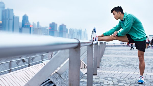 Shot of a young asian man warming up for a jog along the Hong Kong skyline