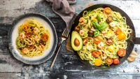 Plate and frying pan of zoodles, avocado, tomatoes, and shrimps