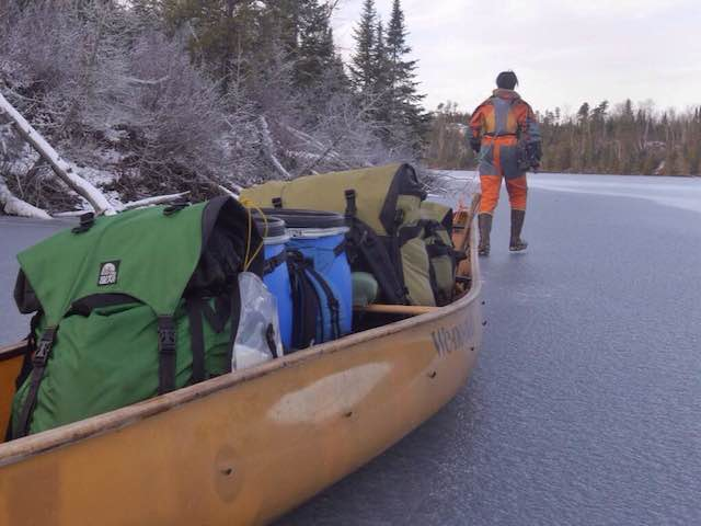 Amy tows the canoe while Dave runs ahead to check the ice.
