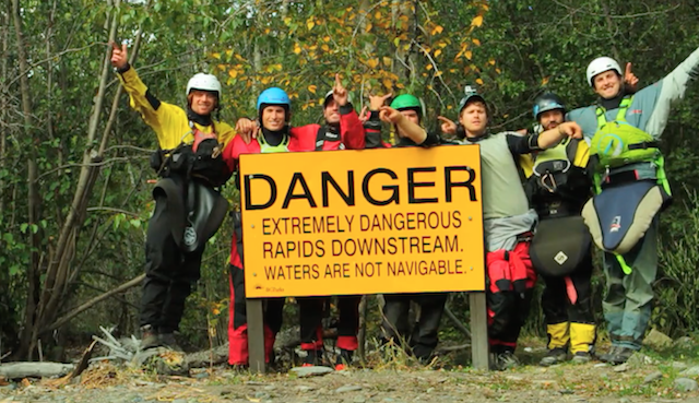 The team poses at the classic warning sign at the put-in.