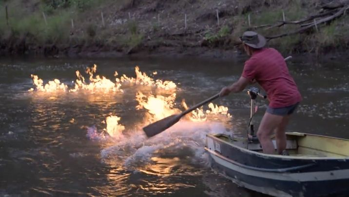 The Condamine River was set on fire by an Australian politician to make a statement. Here a man uses a paddle in an attempt to extinguish the flames.