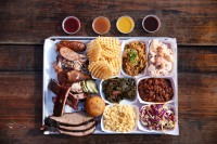 A full BBQ platter with Mac and cheese, cole slaw, beans, greens, potato salad and fries.