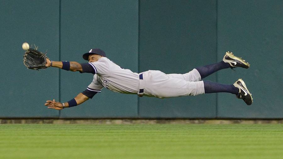 Curtis Granderson #14 of the New York Yankees makes a diving catch in the sixth inning of Game Four of the American League Division Series against the Detroit Tigers at Comerica Park on October 4, 2011 in Detroit, Michigan. The Yankees defeated the Tigers 10-1. (Photo by Mark Cunningham/MLB Photos via Getty Images)