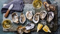 Open Oysters Fines de Claire on stone plate with lemon