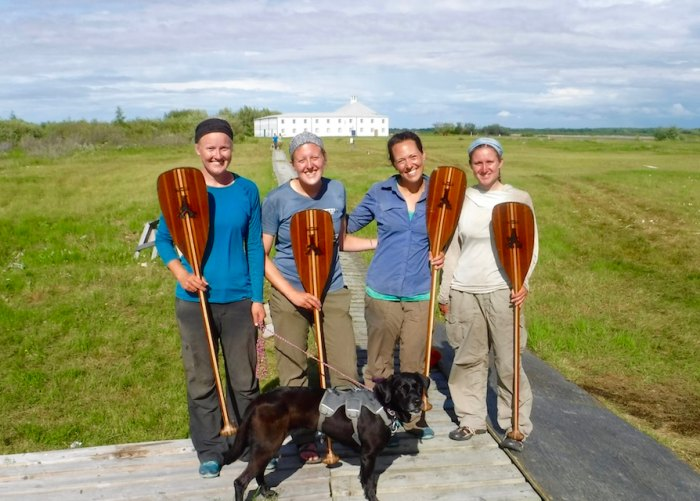 The group holding branded paddles at York Factory. (Steph, Chelsea, Tessa, Whitney & Avery the Dog)