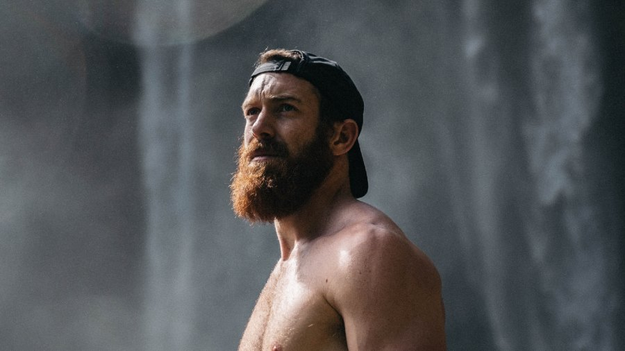 Shirtless man with full beard and backwards baseball hat standing in front of waterfall