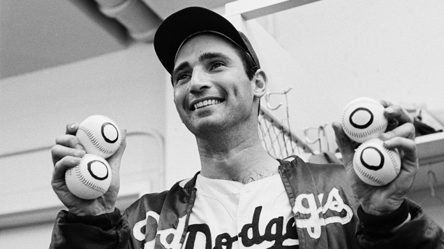 9/9/1965-Los Angeles, CA: In the dressing room late 9/9, Dodgers' pitcher Sandy Koufax holds up four balls with zeros on them, one for each of his no-hitters. Koufax threw his fourth no-hitter and downed the Chicago Cubs, 1-0, with a perfect game.