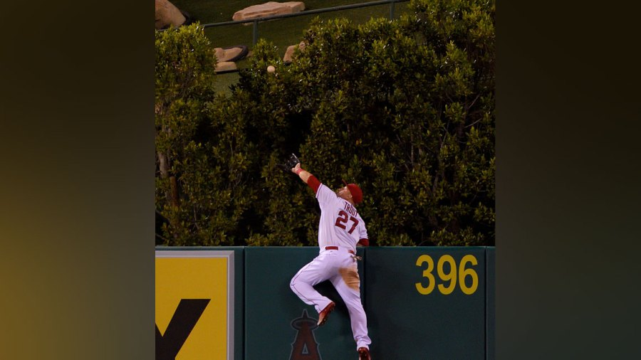 Mike Trout #27 of the Los Angeles Angels of Anaheim makes a catch high over the wall to rob Jesus Montero of the Seattle Mariners of what would have been a three-run home run during the fourth inning of the game against the Seattle Mariners at Angel Stadium of Anaheim on September 26, 2015 in Anaheim, California. (Photo by Matt Brown/Angels Baseball LP/Getty Images)