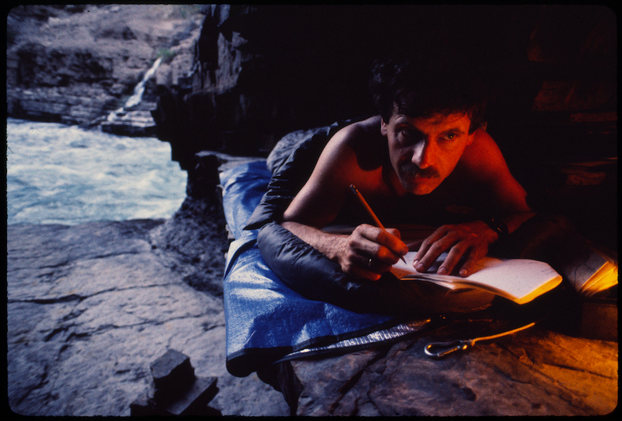 Piotr Chmielinski writes in his diary in a cave at the bottom of Colca Canyon. Photo by Zbigniew Bzdak