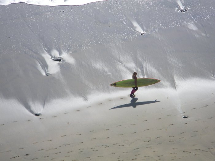 woman heading out to surf between men's heats in 2010