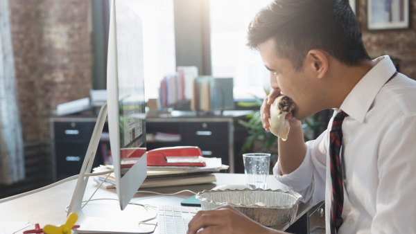 Man eating burrito at office desk