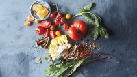 Wild greens, lentils, tomatoes, wild mushrooms, and sage against blue backdrop