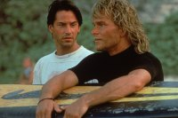 Lebanese-born American actor Keanu Reeves and American actor Patrick Swayze stand on a beach as Swayze holds a surfboard during the filming of the action movie 'Point Break' directed by Kathryn Bigelow, 1991. (Photo by Richard Foreman/Fotos International/Getty Images)