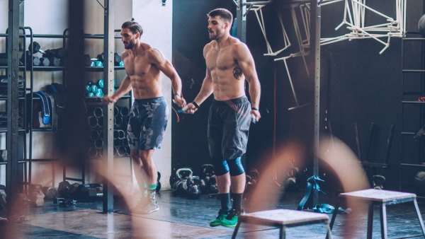 Young men exercising with skipping rope in gym. Professional athletes. Wearing sports clothing.