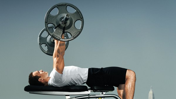 Man bench pressing barbell outdoors