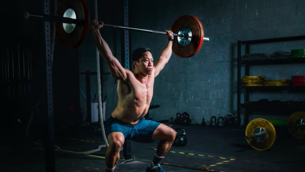 Fit man performing a barbell snatch in the gym