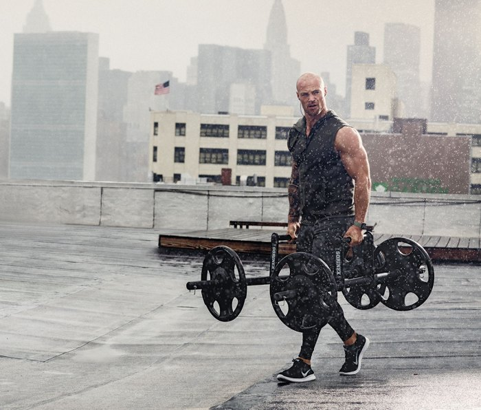 Man doing farmer's carry with hex bar deadlift on rooftop in the rain