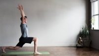 A male yoga instructor does a pose at an indoor yoga studio.