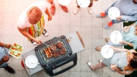 Group of young people having fun at barbecue party in a backyard. Man with apron grilling and giving meats to his friends. African man holding salad. They are enjoy spending time together. Top view.