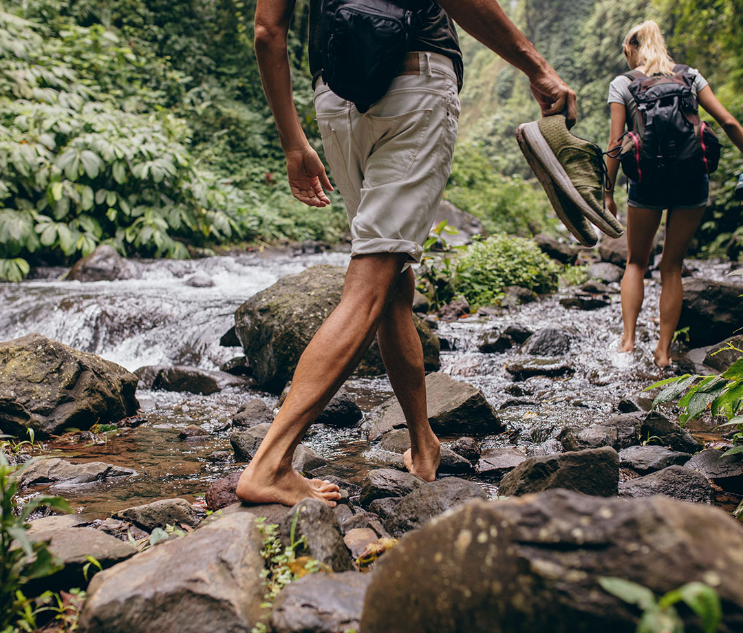 couple hiking barefoot by creek