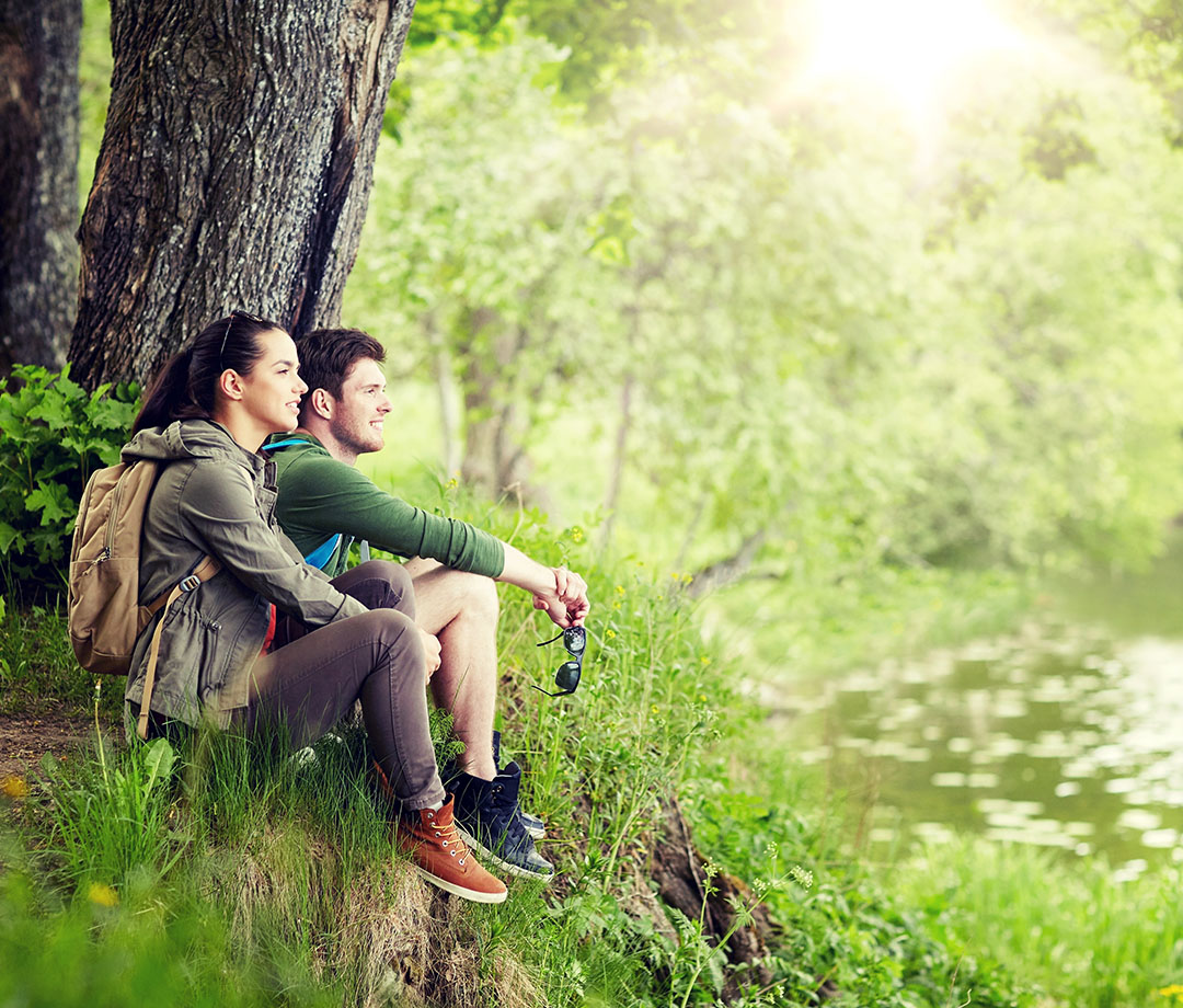 a couple resting by a lake in a forest