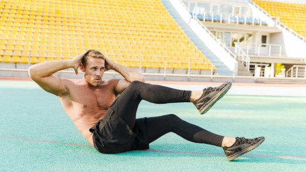 Man doing abs exercise at stadium track
