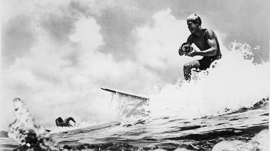 American surfer and director Bruce Brown surfs a wave and holds a camera while filming footage for his international surfing documentary, 'The Endless Summer,' circa 1966. Another surfer rides in the background.
