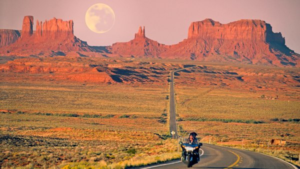 Motorcycle rider in Utah with full moon in background